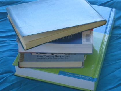 stack of books on blue fabric
